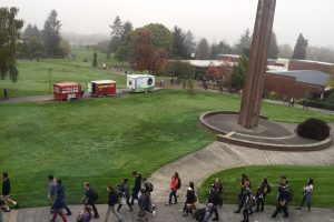 The Clark bell tower adn students walking along a path.