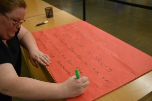 Member of Phi Theta Kappa prepares a poster for the #MeToo display. Theresa Matthiesen/The Indy
