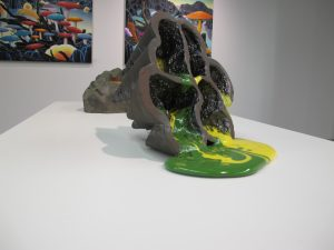 """A plant oozing out a green and yellow substance, as if it was dying. Created by Dylan Beck, made with ceramic and and glass, this piece is called """"Orygun."""" (Dylan Turk/The Independent)"""