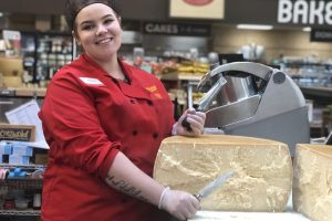 Olivia Chambers working her cheese master job at Fred Myer (Cat Duque/The Indy)