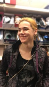 Iris Louie, transgender woman smiles, wearing black and purple clothing. She is standing in a shoe store.