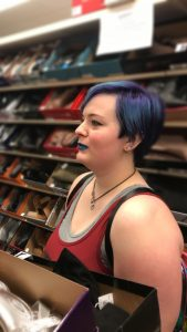 Riah Thomson, a non-binary person looks for shoes for prom. They have purple hair, dark lipstick, grey and red layered tank-tops