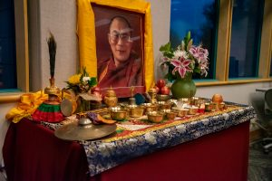 an alter table holds bowls of water, rice, incense, and flowers. The alter to the Dalai Lama holds a photo of him.