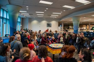 A large crowd gathers around the mandala in the library for the closing ceremony