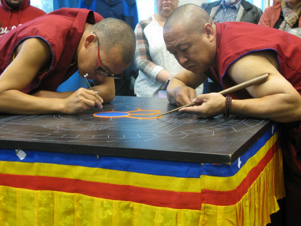 Image shows 2 monks using tools to create sand mandala on table.