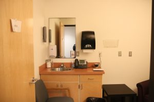 This is an image of the second exam room and shows a sink, a place to sit, and electrical outlets which is everything necessary for pumping milk on the go.