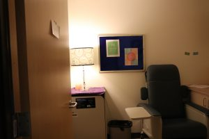 This is an image of one of the two physical exam rooms it shows a physical exam chair meant and counter space.