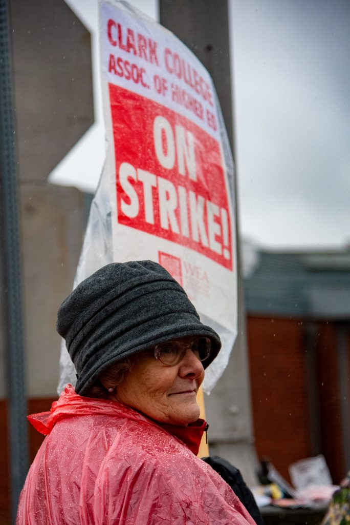 Mitzi Schrag stands out front of Clark College with a picket sign slung over her shoulder.