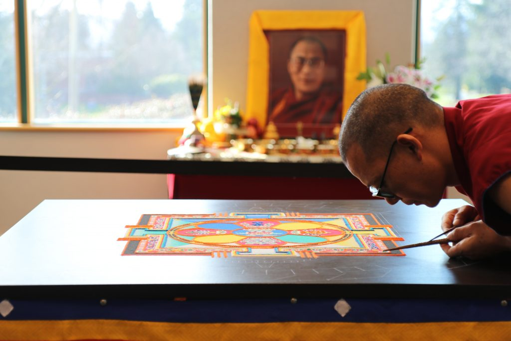 A monk leans over a partly built sand mandala with an altar to the Dalai Lama in the background.