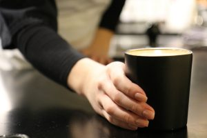 A barista is passing a latte to a customer in a small reusable cup.