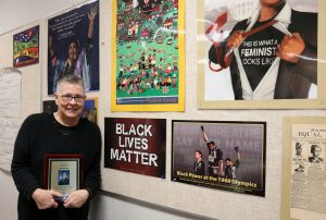 Image shows Diane Ulner holding their Lora Whitfield award in the main Women's Studies room with various posters advocating for social equity on the wall behind them.