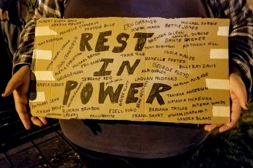 """Eden holds a sign that pays tribute to victims of police brutality over the years, """"I want them to rest in power and in peace"""" (Matt Fields/The Indy)"""