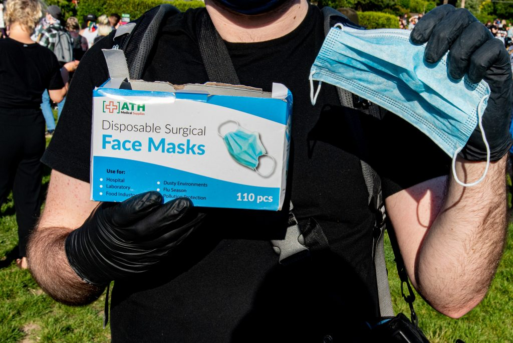"""Tuesday June 2 protester Danny handed out face masks to those who needed them while assembling. When asked what type of a response he was getting, he responded """"People are grateful... I've passed out about 200 of them, people seem to have a need.""""(Matt Fields/The Indy)"""