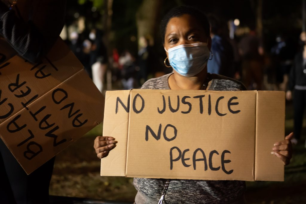 Ramonia holds her sign while masked at Chapman Square on June 4. She has been to many protests in Portland but feels the tone of those following the death of George Floyd are different. (Matt Fields/The Indy)