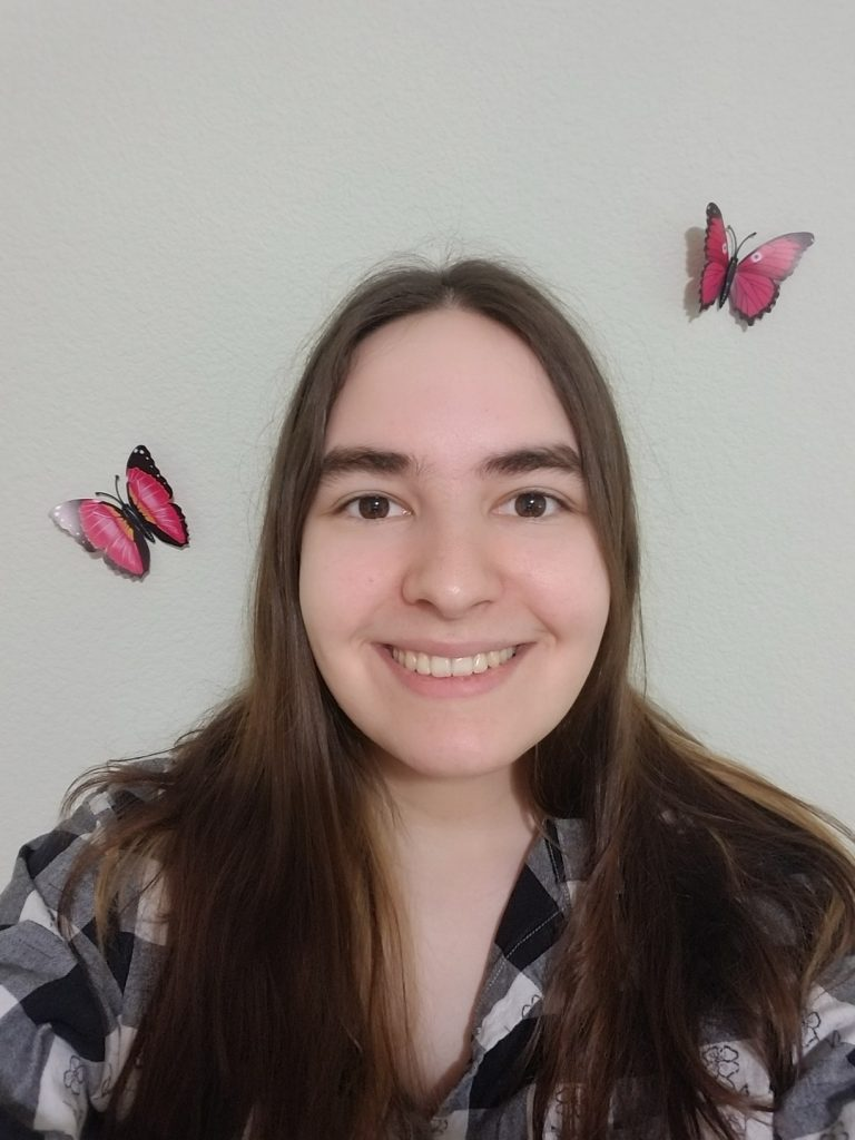 Image of Krystal Dake with a filter that has two pink butterflies fluttering around her.