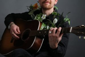 Garrett Mann sitting in a chair, playing guitar and wearing a flower Lei