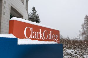 Photo of the Clark college sign. The sign has snow cover the top.
