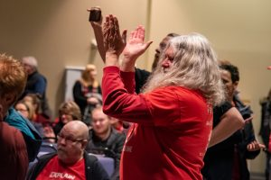 Faculty members in red applaud the vote to approve a new union contract