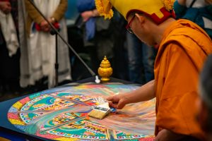 A monk brushes away an intricate sand mandala