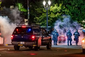 Law enforcement officers walk through a cloud of smoke while pushing protesters out of Chapman Square on June 5 in downtown Portland.(Matt Fields/The Indy)
