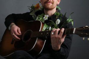 Garrett Mann sitting in a chair, playing guitar and wearing a flower Lei