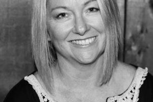 Black and white photo of a lady who has straight blonde hair with a black and white top.